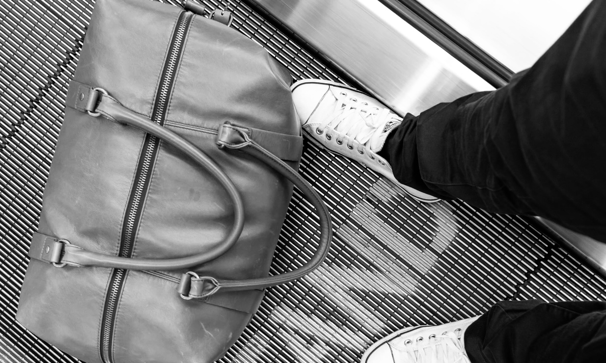 Standing on a moving walkway in an airport with luggage