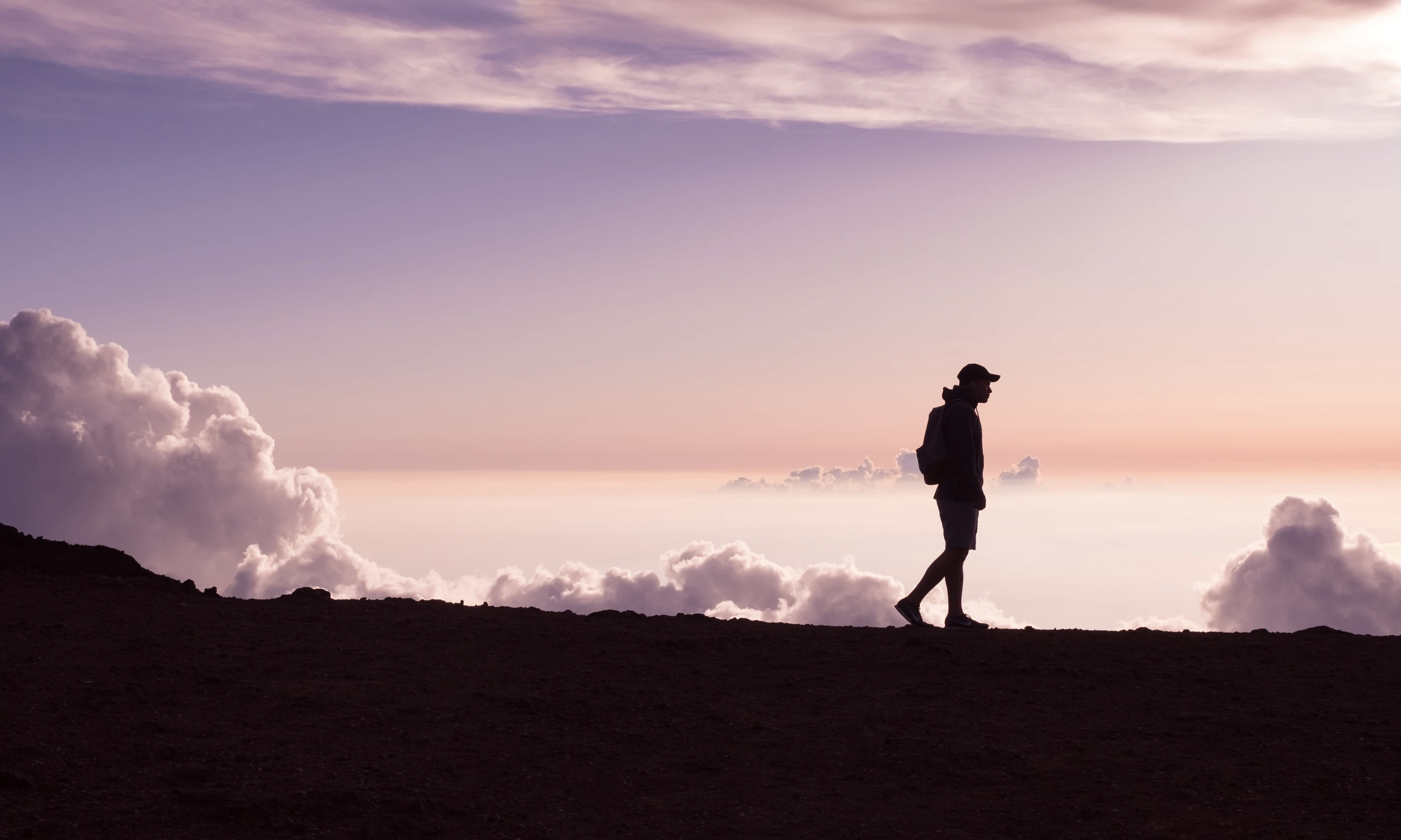 Silhouette of Man Walking in Front of Clouds